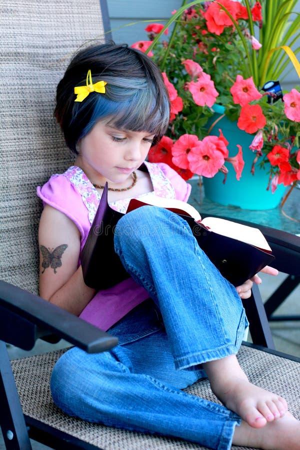 Little yuppie girl reading book stock photo