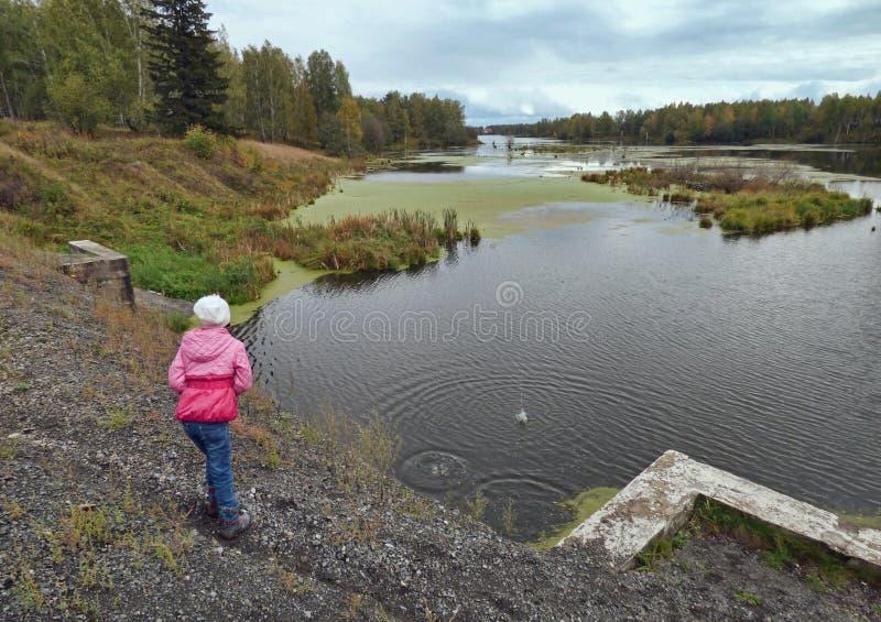 Littlle dziewczyny throwin kamienie w wodzie od wysokiego banka obraz royalty free