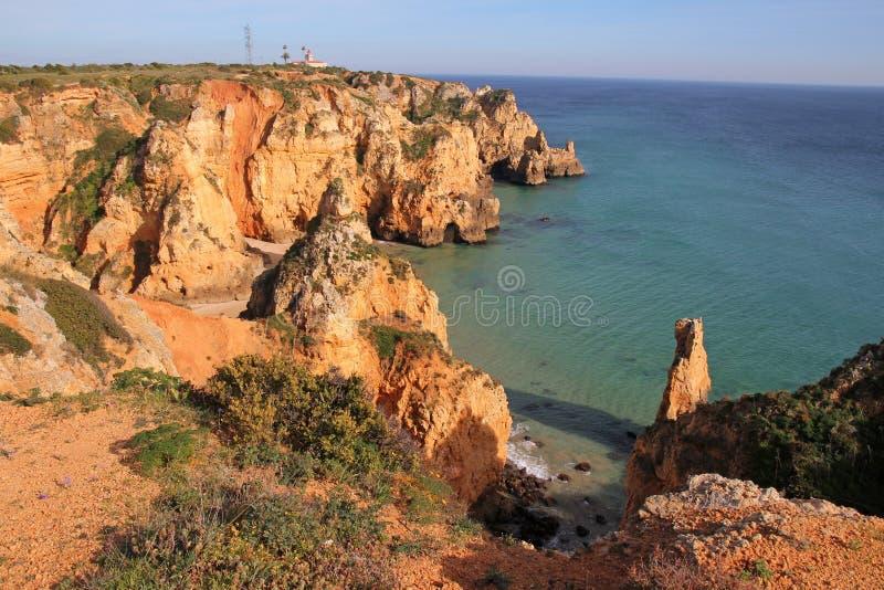 Littoral de falaise avec le phare à Lagos, Algarve, Por image stock