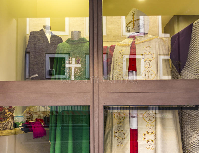 Liturgical garments in a shop window in Vatican. VATICAN CITY, VATICAN - DEC 23, 2015: liturgical garments in a shop window in Vatican city for catholic priests stock image