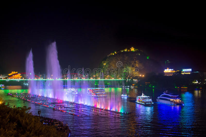 LIUZHOU, CHINA - SEPTEMBER 28, 2016: Music fountain on the Liujiang river with boats and karst formations. LIUZHOU, CHINA - SEPTEMBER 28, 2016: Music fountain on royalty free stock image