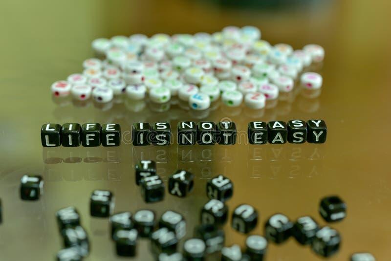 LIV ÄR INTE LÄTT skriftligt med den svarta kuben för akryl med vita alfabetpärlor på exponeringsglasbakgrunden royaltyfri fotografi