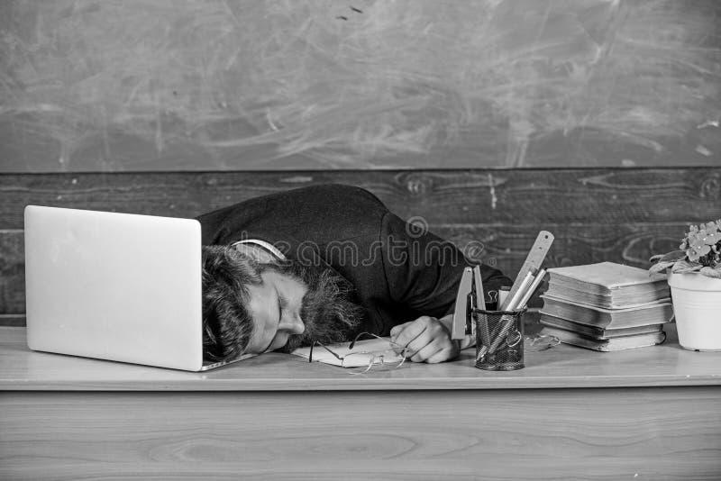 Liv av att evakuera för lärare Fall sovande på arbete Mer stressad arbete för utbildare än genomsnittligt folk Skäggig man för ut royaltyfria bilder
