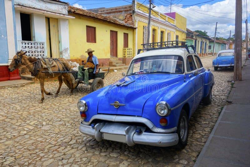 Liv för gata för stad för medel för taxi för bil för klassiker för gamal manhästvagn kubanskt Trinidad Cuba arkivfoton
