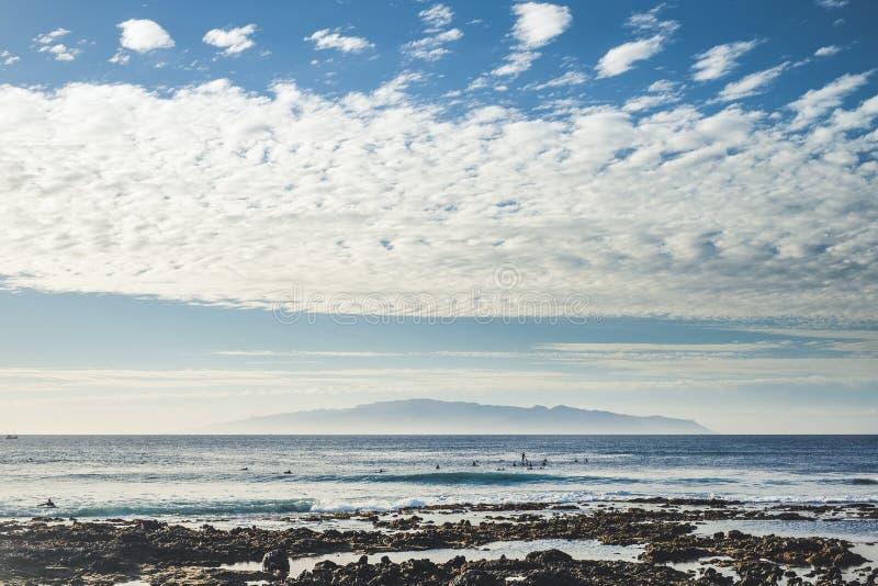 Liv för kusthavstrand med lotten av surfare som utbildar på vattnet och vågorna - blått landskap med havet och öar i bakgrund arkivbild