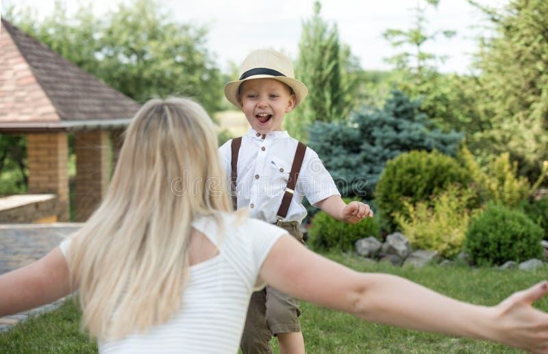 Liv?gonblick av den lyckliga familjen! Moder- och sonbarn som tillsammans spelar ha gyckel p? gr?set i solig sommardag fotografering för bildbyråer