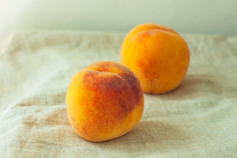 Liv med färsk persika med linne och tyg på träbord. Ljusstark sommarfrukt, flatlägg arkivfoto