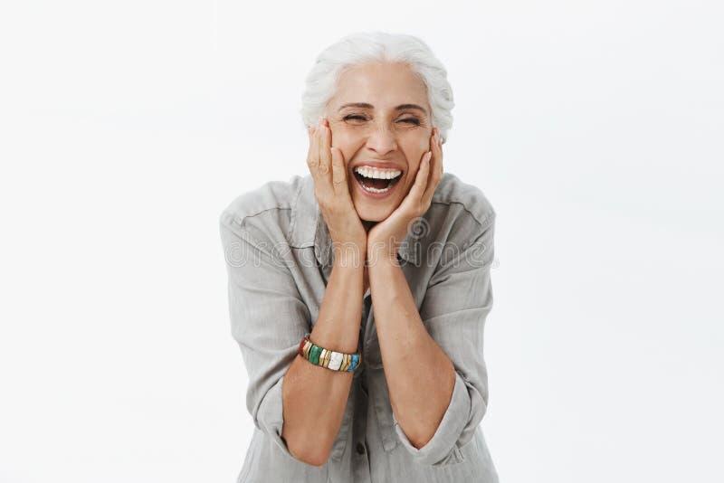 Liv startar endast när att få äldre Stående av att charma den lyckliga och bekymmerslösa europeiska höga kvinnan med grått skratt royaltyfri fotografi