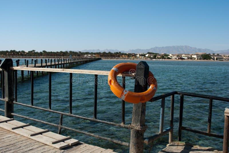 Livboj och pir Orange livboj på barriärpelare Räddninglivboj och blått vatten Säkerhetsutrustning på skeppsdockan för nödläge arkivfoton
