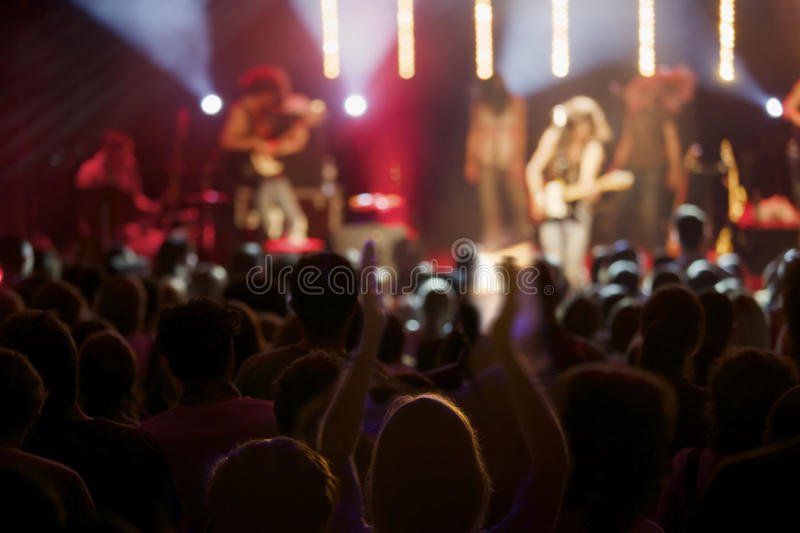 Live act of rock band on stage with audience. Band on stage giving live concert with fan cheering in foreground, some motion blur at arms stock photo