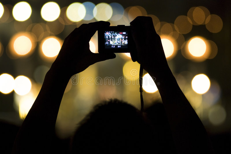 Live concert. Shot in a shot of a compact camera with bokeh effect of background lights - man taking a picture of a concert - Concert of Peter Gabriel in Venice royalty free stock photo