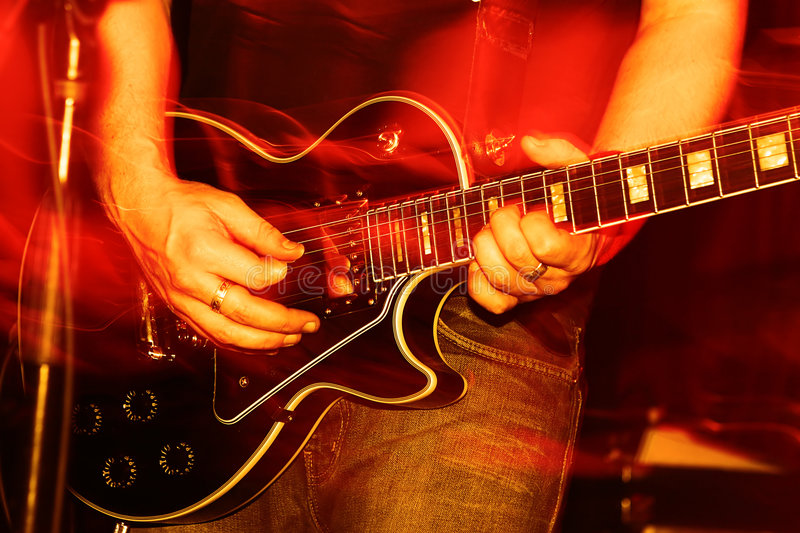 Live Concert. Closeup of an guitarist at a rock concert, motioneffect royalty free stock photo