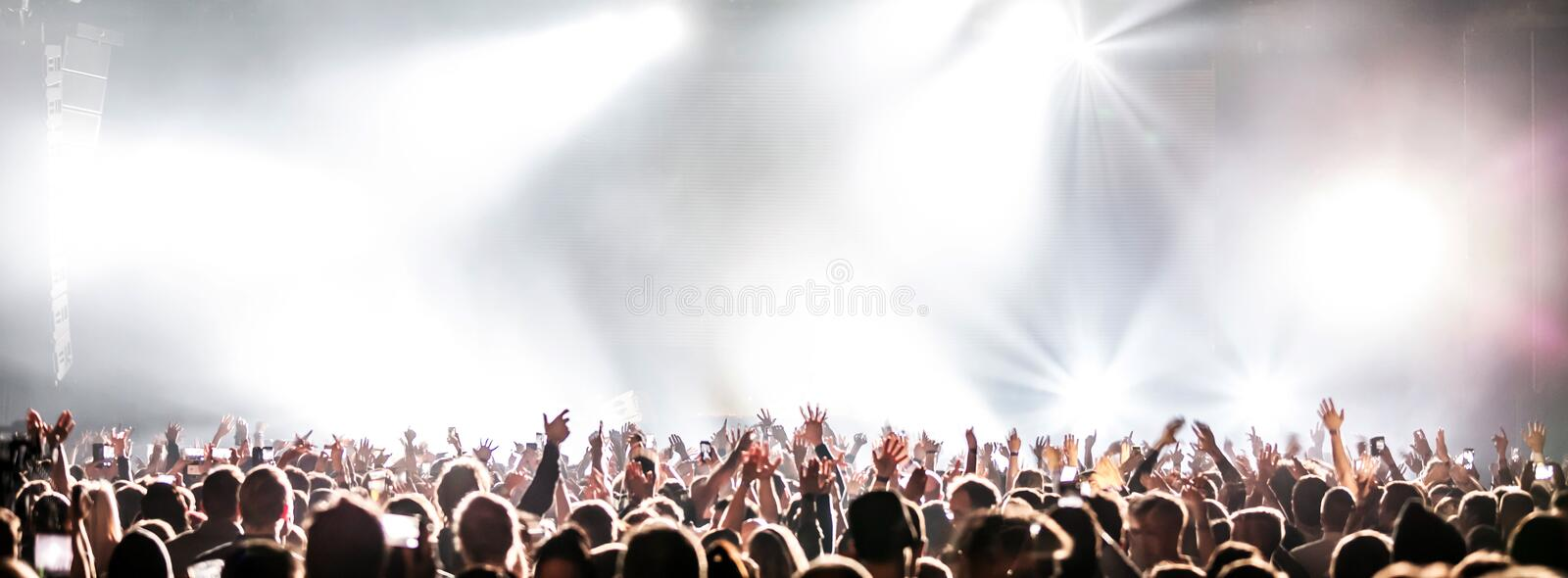 Live concert with raising hands. Silhouettes of concert crowd in front of bright stage lights stock photo