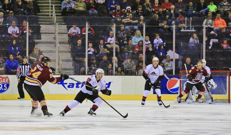 Live Hockey action. Pro hockey players skate to retrieve the loose puck stock image