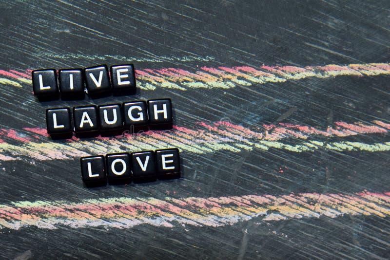 Live Laugh Love sur les blocs en bois Image traitée croisée avec le fond de tableau noir images libres de droits