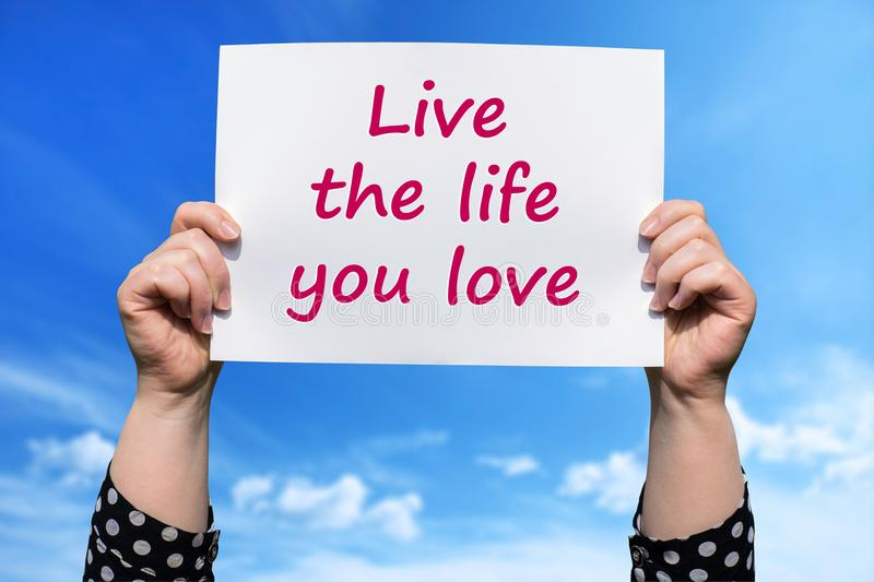 Live the life you love. Motivational sign woman holding by hand royalty free stock photo