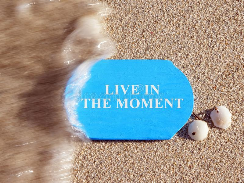 Live in the Moment sign on a blue plate royalty free stock photos