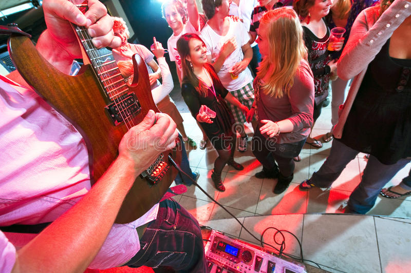 Live music. Guitarist maxing out on his guitar with a large group of people on the dance floor in a nightclub royalty free stock images