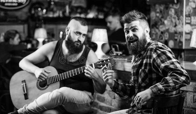 Live music concert. Acoustic performance in pub. Hipster brutal bearded with friend in pub. Man play guitar in pub. Cheerful friends sing song guitar music royalty free stock photo