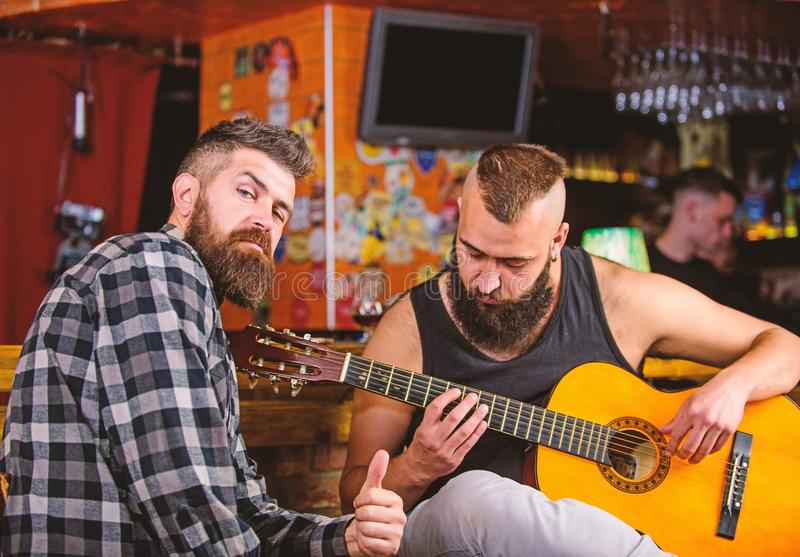 Live music concert. Acoustic performance in pub. Hipster brutal bearded with friend in pub. Cheerful friends sing song. Guitar music. Relaxation in pub stock photos