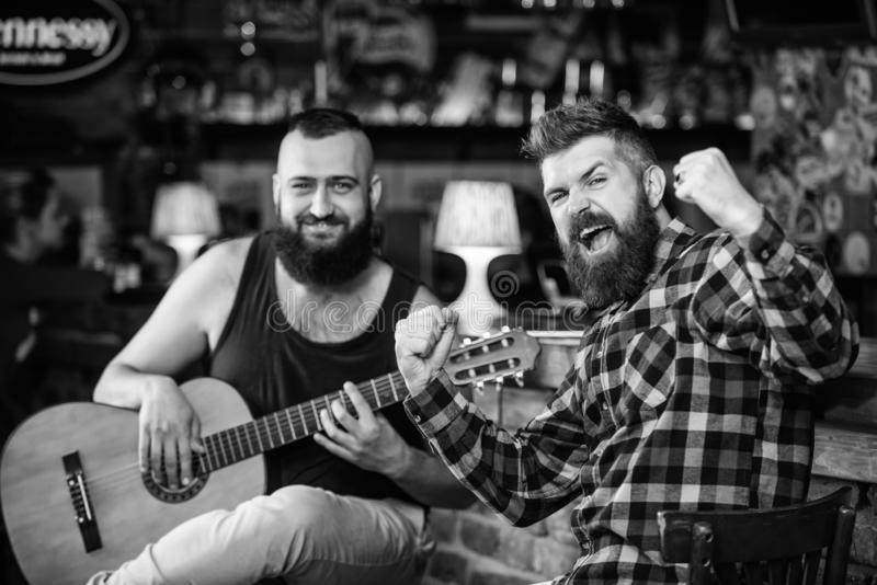 Live music concert. Man play guitar in pub. Acoustic performance in pub. Hipster brutal bearded with friend in pub. Cheerful friends sing song guitar music royalty free stock photography