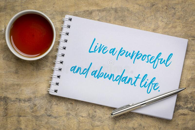 Live a purposeful and abundant life. Inspirational handwriting in a sketchbook with a cup of tea, success, happiness and personal development concept stock photos