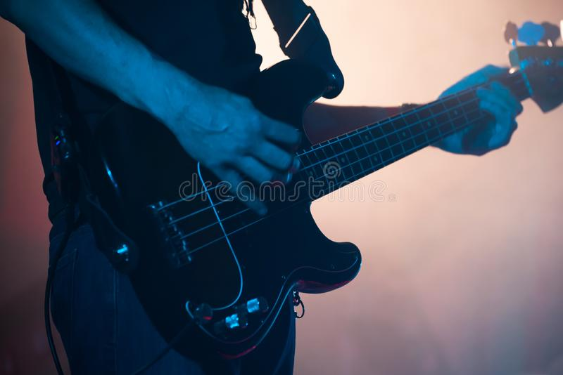 Live rock music background, bass. Live rock music background, electric bass guitar player in blue stage lights, closeup photo with soft selective focus stock photography