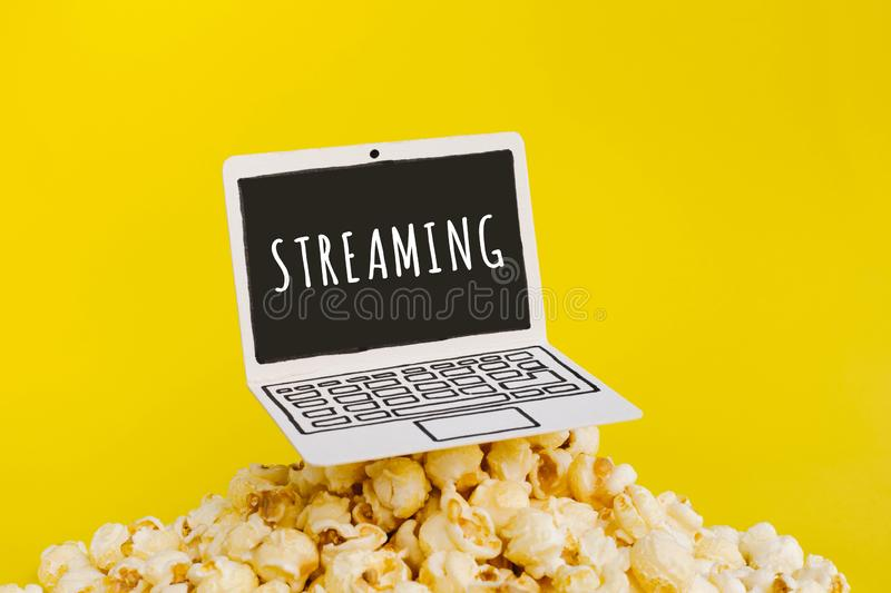 Live streaming concepts with text on paper art laptop and.pop corn on pastel color. Background royalty free stock image
