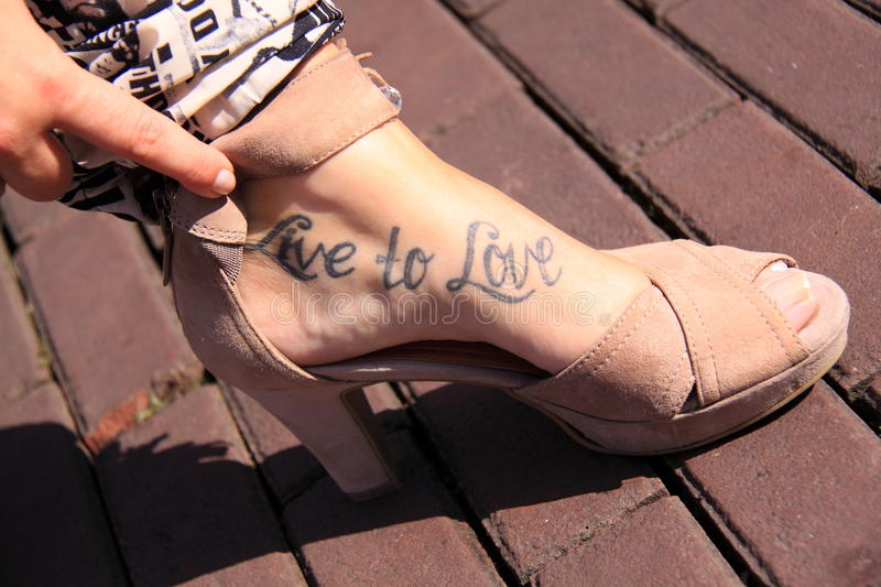 Live to love tattoo. Tattoo on female foot wearing open toe high heels shoe with the words live to love royalty free stock image