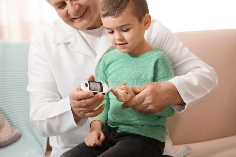 Livello della glicemia del paziente di misurazione di medico con il metro digitale del glucosio a casa Controllo del diabete fotografia stock libera da diritti