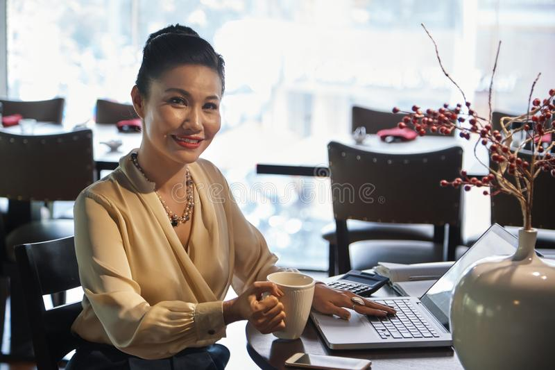 Cheerful businesswoman sitting in cafe with laptop stock image