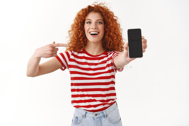 Lively charismatic cheerful redhead female promote awesome app extend arm camera show smartphone screen pointing gadget. Display smiling broadly asking friend stock photography