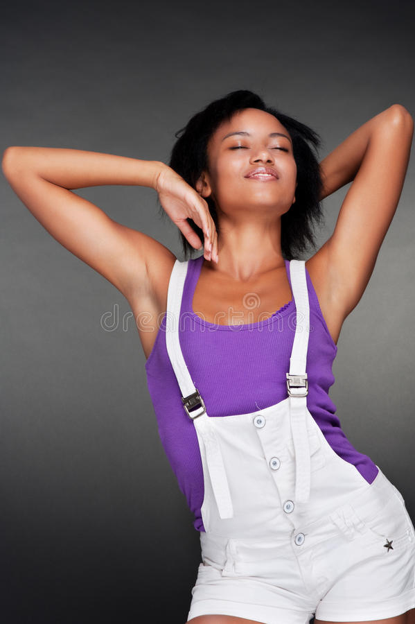 Lively woman in white shorts. Posing against dark background stock photography
