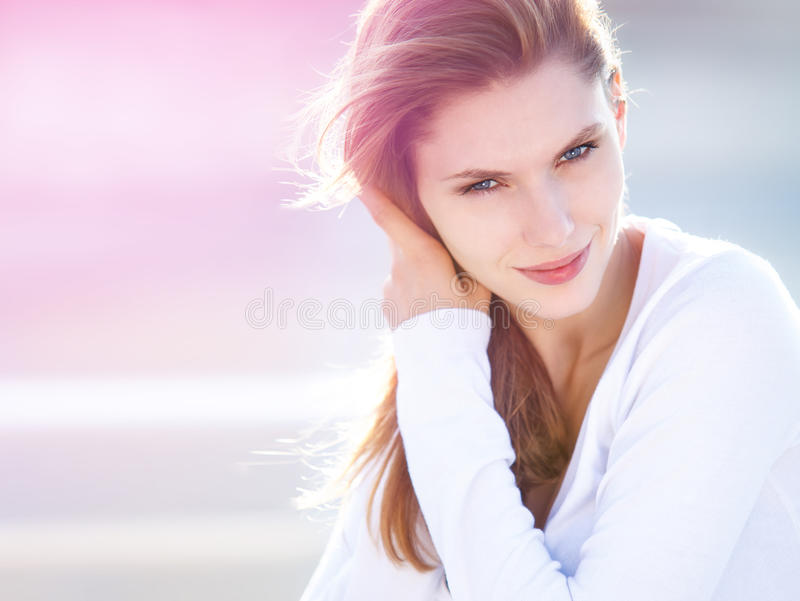 Lively young woman touches her hair. Magnificent brunette smiling girl is straightening her hair stock image