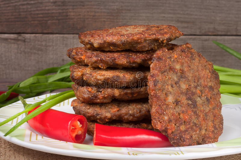Liver pancakes or cutlets with chili pepper and green onions on a wooden background.  stock images