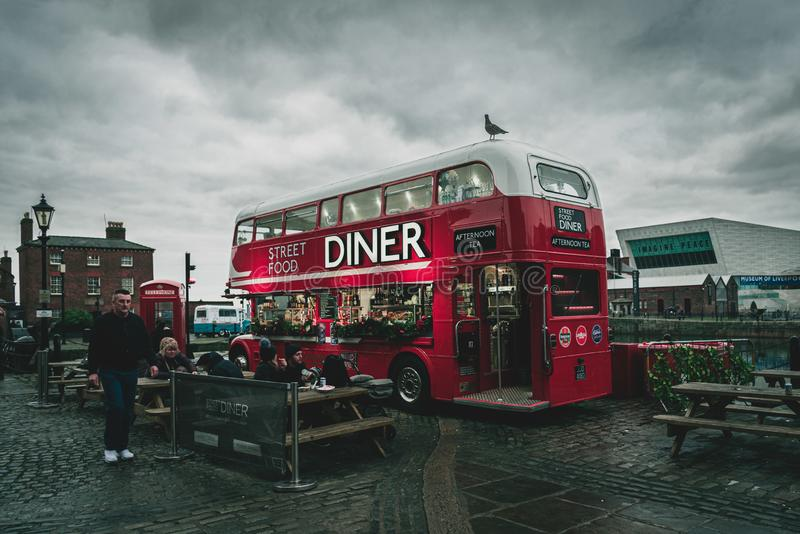 LIVERPOOL, ENGLAND, DECEMBER 27, 2018: People enjoying a meal on a cloudy day, beside a red double decker bus as food truck,. Decorated for christmas time royalty free stock photos