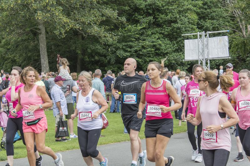 Race for Life sponsored fun run. Liverpool, UK - June 8, 2019: Race for Life sponsored fun run for British charity Cancer Research UK. The race is on, Groups and royalty free stock photos