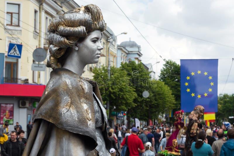 Livestatue der Königin vor dem hintergrund der Leute, der Gebäude und der Flagge der Europäischen Gemeinschaft stockfotografie