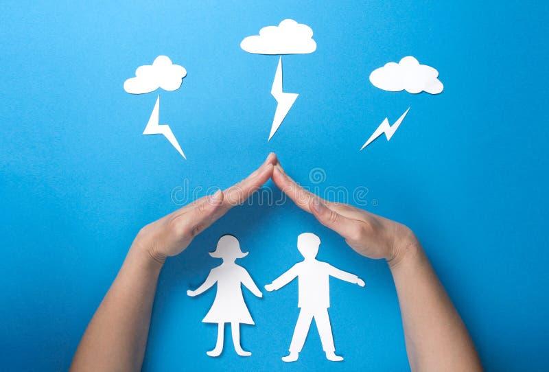 Livförsäkring och familjhälsobegrepp Händer skyddar pappers- diagram origami från blixt från molnen på blå bakgrund arkivbilder