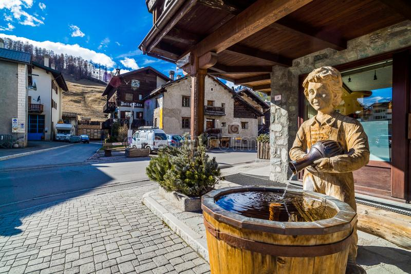 Traditional Alpine wooden architecture, fountain and sculpture, Livigno, Alps stock image