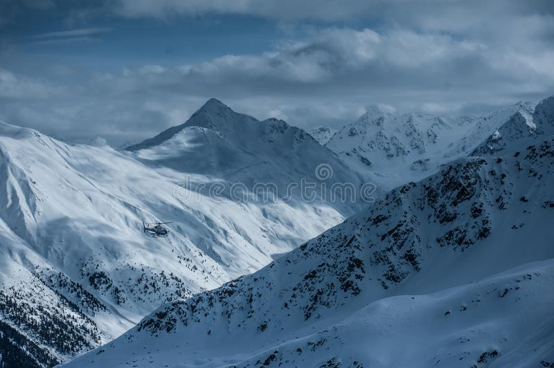 Livigno Italy, snow covered mountains with Helicopter. Livigno is a ski resort in the Italian Alps, near the Swiss border. It`s known for its snow parks, with royalty free stock photography