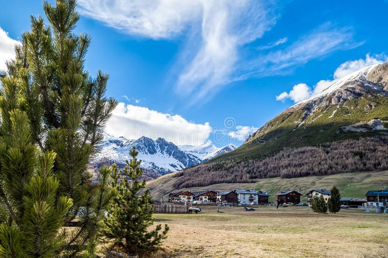 Livigno village, street view with old wooden houses, Italy, Alps. Livigno village, Italian Alpine ski and resort centre, street view with old wooden residential royalty free stock image