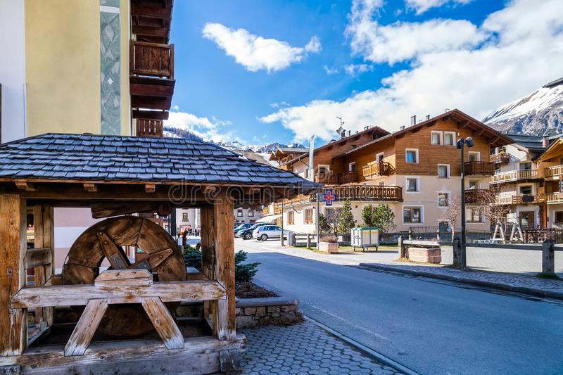 Livigno village, street view with old wooden water wheel, Italy, Alps. Livigno village, Italian Alpine ski resort centre, street view with old wooden water wheel stock images