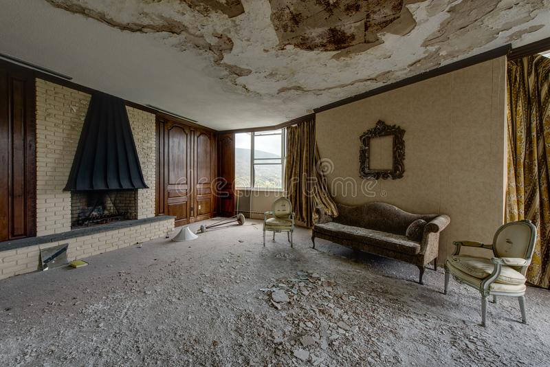 Living Area with Fireplace, Couch & Chairs - Abandoned Nevele Resort - Catskill Mountains, New York. A view of a top floor penthouse room with a fireplace stock photos