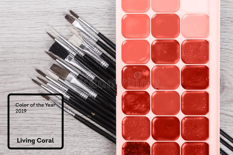 Living Coral color of the Year 2019. Paintbrush on a palette color guide with coral in trendy color.  royalty free stock images