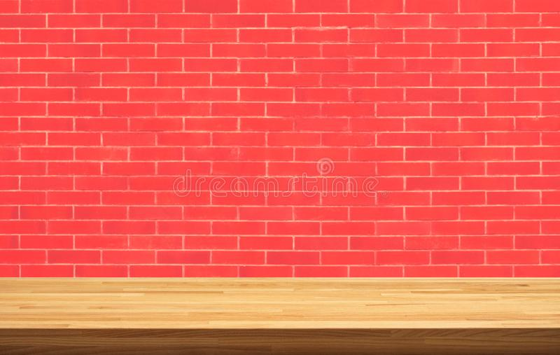 Living Coral color year 2019 with wood table top on brick wall royalty free stock image