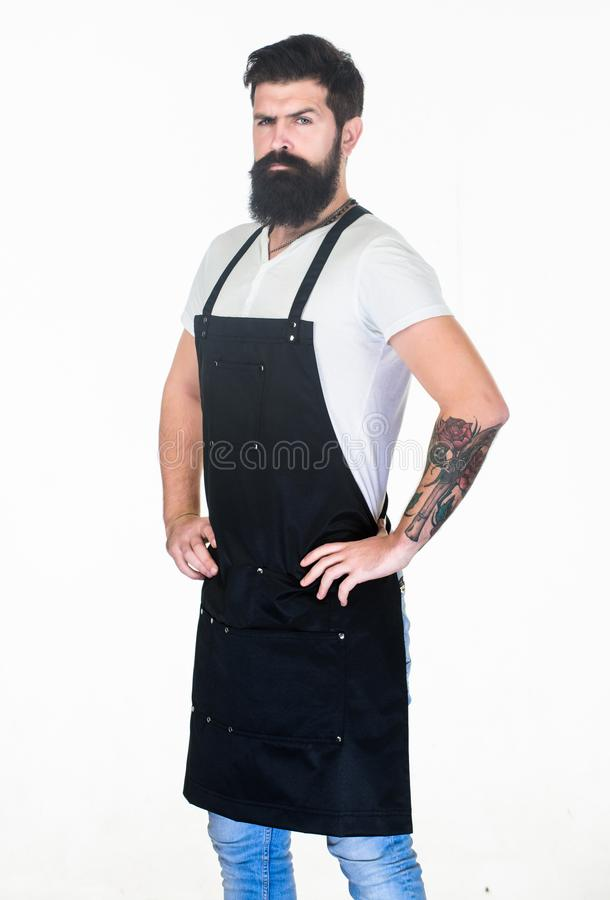 Living hipster lifestyle. Hipster with long beard and mustache in work apron. Bearded hipster wearing barber or cooking stock images