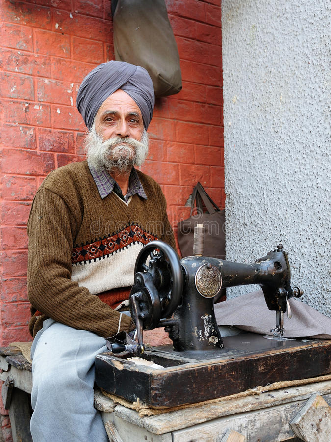 Living in India. INDIA, AMRITSAR - 02 DECEMBER 2009: Tailor with the sewing machine repairing clothes in streets of Indian cities stock photography