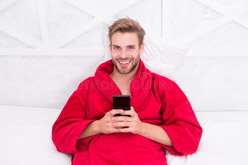 Living a mobile lifestyle. Cheerful guy using mobile device in bed. Handsome man smiling with mobile phone in hands stock image