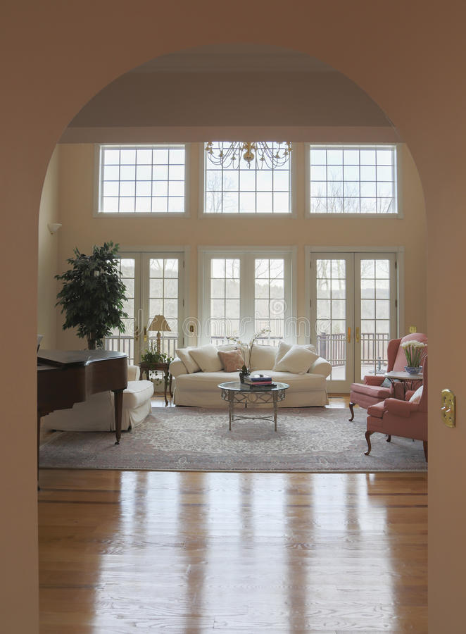 Living Room Archway. A view of a bright formal living room from an arched doorway royalty free stock image